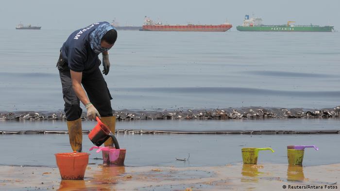 A policeman scoops oil from a beach (Reuters/Antara Fotos)
