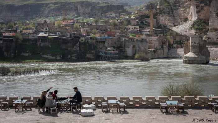 Tourists point at destroyed rock cliffs and earthworks in Hasankeyf, an ancient settlement in southeast Turkey being primed for flooding