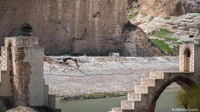 Construction crews move rubble on the banks of the Tigris River between the pillars of a historic Silk Road bridge