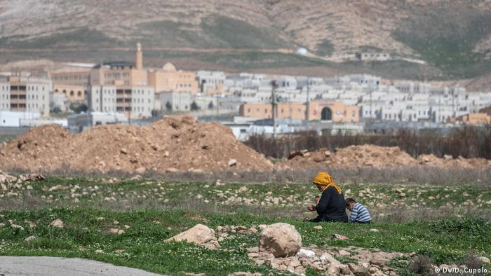A woman and child sit in front of the new Hasankeyf, which will replace the original Hasankeyf once water levels rise
