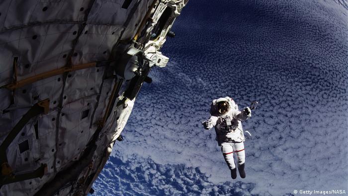 Astronaut schwebt in der Nähe von Satellit