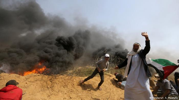 Palestinians remove part of the Israeli fence at the Israel-Gaza border during clashes at a protest demanding the right to return to their homeland. Thick black smoke is seen in the background. (Reuters/I. A. Mustafa)