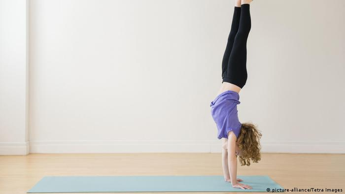 Mädchen macht einen Handstand (picture-alliance/Tetra Images)