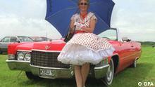Birgit Formella steht am Sonntag (12.07.98) mit Regenschirm vor ihrem Ami Schlitten, einem Cadillac de Ville Baujahr 1969. In Owschlag (Kreis Rendsburg Eckernförde) ist Birgit, die Kleidung und Autos der 60ziger Jahre liebt, wettermäßig für alle Fälle gerüstet. Ob Wind, Regen oder Sonne sie hat die passenden Utensilien für eine Sonntagstour im Kofferraum. dpa COLOR