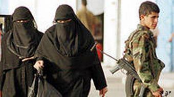 Yemeni women in Islamic covered dress pass a young soldier with his AK-47 submachine gun in Sana.