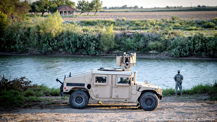 A soldier from the Texas Army National Guard observes a section of the Rio Grande along the Texas-Mexico border