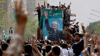 Supporters of reformist presidential candidate Mir Hossein Mousavi carry his poster, during a rally in Tehran