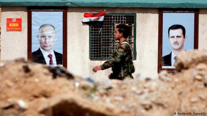 صورة بوتين إلى جانب صورة بشار الأسد في أحد جبهات القتال في الغوطة (أرشيف)