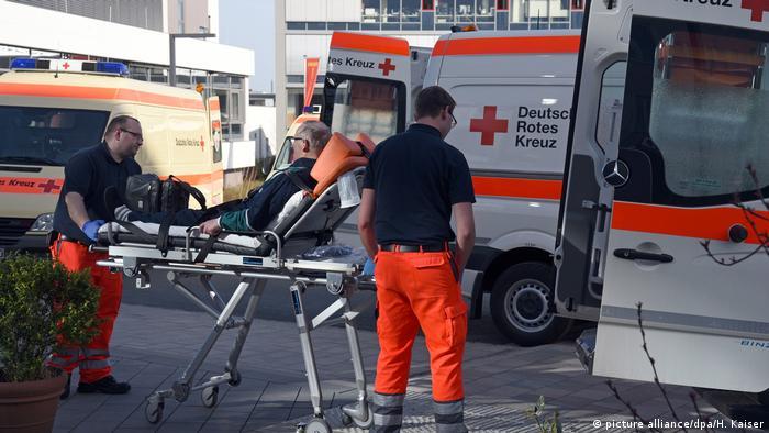 Пациента на каталке доставляют к карете скорой помощи
