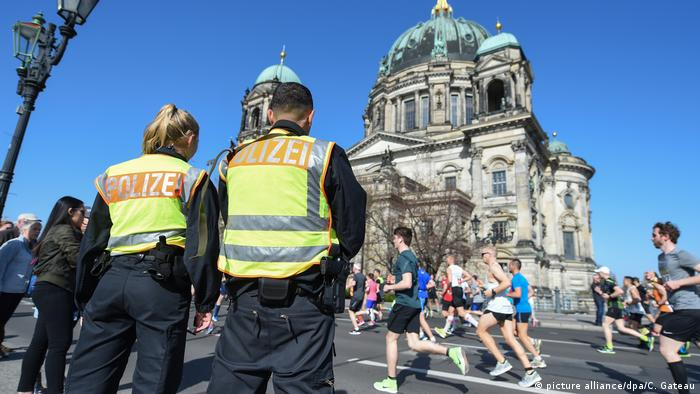 Police watch runners at the Berlin Half Marathon