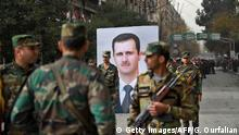 Syrian soldiers walk past a portrait of President Bashar al-Assad during a government celebration marking the first anniversary of the retaking of the northern Syrian city of Aleppo, near the square of Saadallah al-Jabiri on December 21, 2017. After a suffocating siege and a crushing offensive which used barrel bombs, rockets and shells, the Syrian army declared in December 2016 it had full control of second city Aleppo. / AFP PHOTO / George OURFALIAN (Photo credit should read GEORGE OURFALIAN/AFP/Getty Images)