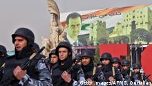 Syrian soldiers march in formation past a banner depicting President Bashar al-Assad during a government celebration marking the first anniversary of the retaking of the northern Syrian city of Aleppo, in its square of Saadallah al-Jabiri on December 21, 2017. After a suffocating siege and a crushing offensive which used barrel bombs, rockets and shells, the Syrian army declared in December 2016 it had full control of second city Aleppo. / AFP PHOTO / George OURFALIAN (Photo credit should read GEORGE OURFALIAN/AFP/Getty Images)