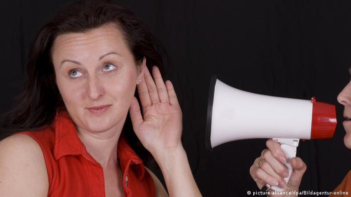 Woman holding her ear to a megaphone (picture-alliance/dpa/Bildagentur-online)