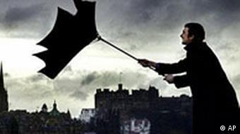 Man with umbrella blown inside out by wind in Edinburgh