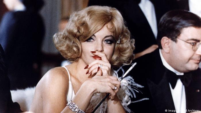 Filmstill Trio Infernal: Romy Schneider in blonder Perücke und mit Zigarette (Imago/United Archives)