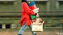 Frau balanciert Geschenke heim.