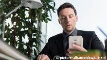 Büro Person mit Smartphone (picture-alliance/dpa/A. Heinl)