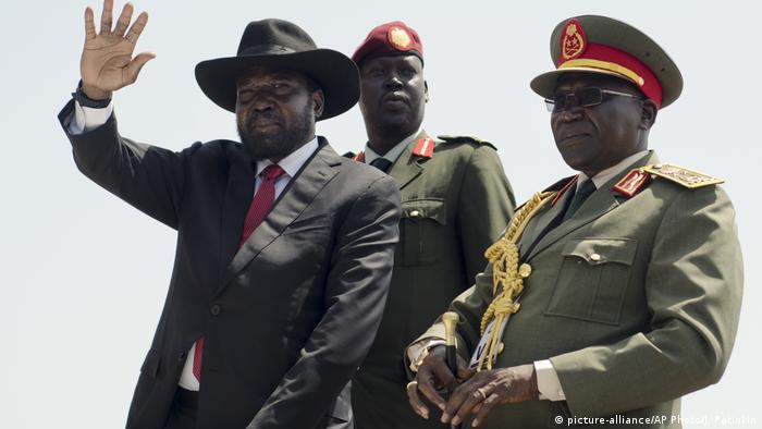 South Sudan's President Salva Kiir, left, accompanied by army chief of staff Paul Malong Awan, right, waves during an independence day ceremony in the capital Juba,