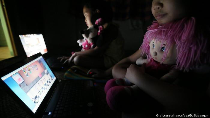 Filipino grade school children play with their computers inside their house in Quezon City, east of Manila, Philippines