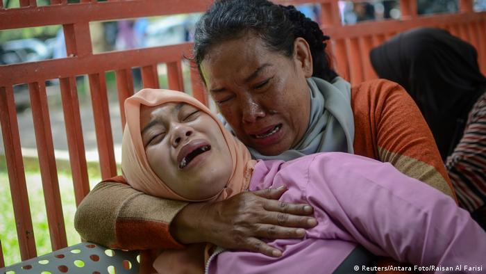 Relatives of man who died after consuming tainted homemade alcohol cry outside of a hospital in Cicalengka, Bandung Regency, West Java, Indonesia.