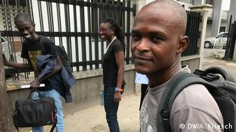 Emeka Udemba stands on the street with his backpack
