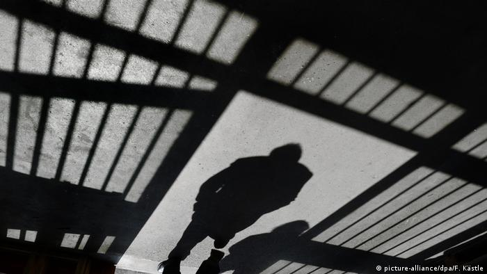 A person's shadow can be seen on the ground alongside the bars of a prison cell
