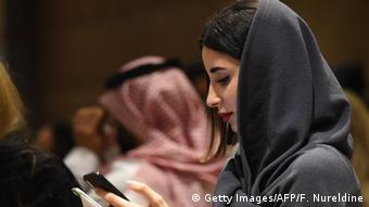 A woman wearing a headscarf is looking at her mobile phone, in the background is a man with a traditional Saudi Arabian headscarf.