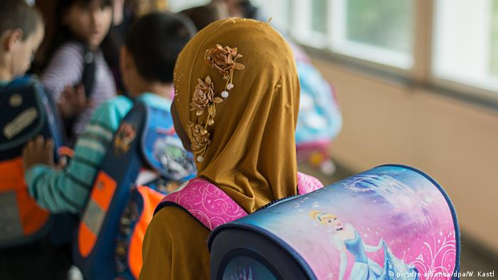 A child wears a headscarf and a backpack while waiting in line at school