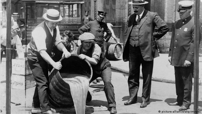 Ню Йорк, 1921: зам.-директорът на полицията Джон А. Лийч (вторият отдясно) наблюдава изливането на конфискуван алкохол в канализацията