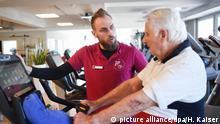 06.04.2018, Nordrhein-Westfalen, Bergisch Gladbach: Trainer Wieland Westhoff erklärt Helmut, 85 Jahre alt, in einem Fitness-Studio den Gebrauch des Fahrrad-Ergometers: Foto: Henning Kaiser/dpa +++(c) dpa - Bildfunk+++ | Verwendung weltweit