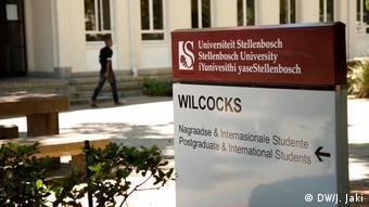 A young man walking past a sign pointing to Stellenbosch University's Wilcocks building