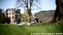 11.04.2018, Baden-Württemberg, Heidelberg: Ein Pärchen sitzt in der Sonne vor dem Heidelberger Schloss. Foto: Sina Schuldt/dpa +++(c) dpa - Bildfunk+++ | Verwendung weltweit