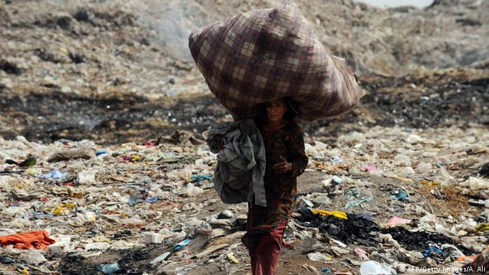 A woman in Pakistan carried used clothing on her head as she walks through a garbage dump area on the outskirts of Lahore