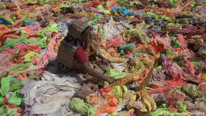 A woman sorts through clothes in Bangladesh