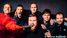 The band members of Feine Sahne Fischfilet, which the frontman holding a lit flare in his mouth