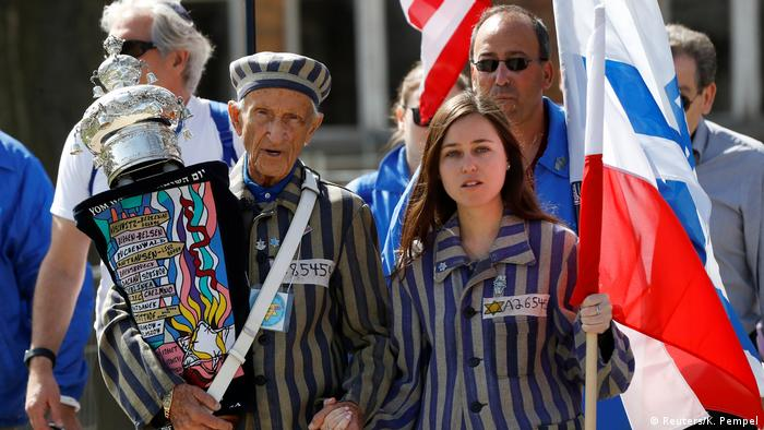 Holocaust survivor Edward Mosberg holds a torah during the March of the Living