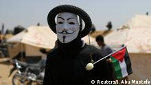 A Palestinian demonstrator wears a mask with a tire during a protest at the Israel-Gaza border in the southern Gaza Strip April 6, 2018. Picture taken April 6, 2018. REUTERS/Ibraheem Abu Mustafa
