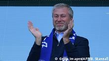 Roman Abramovich claps at a Chelsea FC match