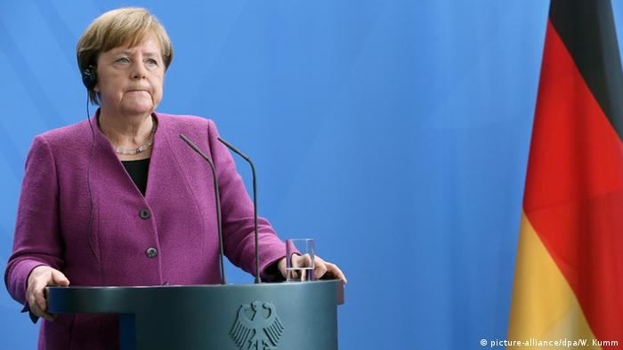 Merkel stands at a podium during a press conference