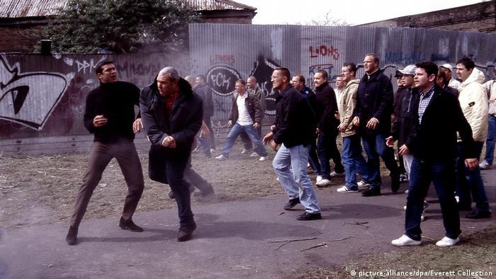 Eine Szene aus dem Film The Football Factory, die eine Gruppe gewaltbereiter Hooligans in einer Gasse zeigt.