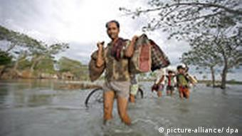 A man wades through floodwaters in Bangladesh