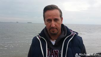 Kriminalhauptkommissar Michael Bahrs steht in ziviler Kleidung am Ufer eines Gewässers.
