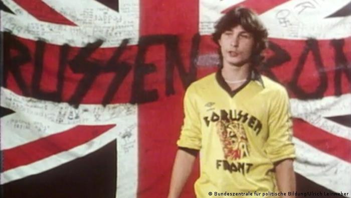 Ein BVB-Hooligan mit gelb-schwarzem Trikot steht vor einer Union-Jack-Flagge mit der Aufschrift Borussenfront. Die Typographie des Buchstaben s ist eindeutig der Siegrune der SS nachempfunden. Auch finden sich Hakenkreuze auf der Flagge wieder.