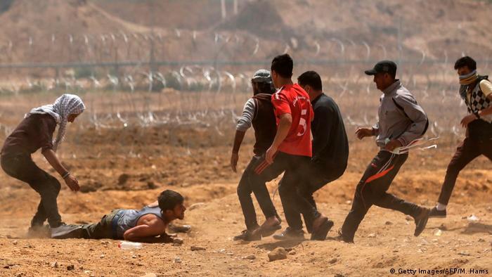 چند فلسطینی در نزدیکی مرز اسرائيل در غزه به کمک فلسطینی دیگری میشتابند که مجروح شده است
