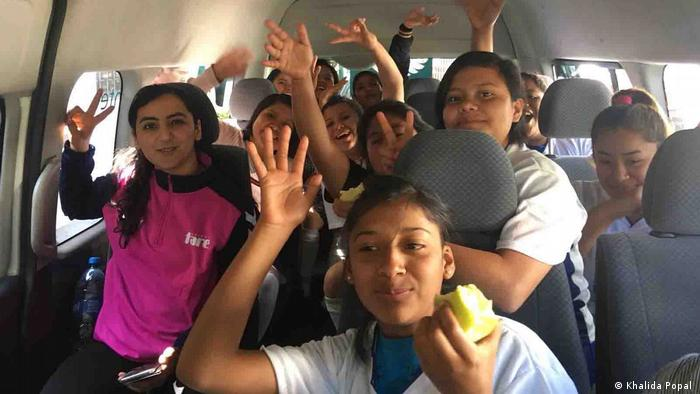 Khalida Popal (left) sitting with several girls in a minibus