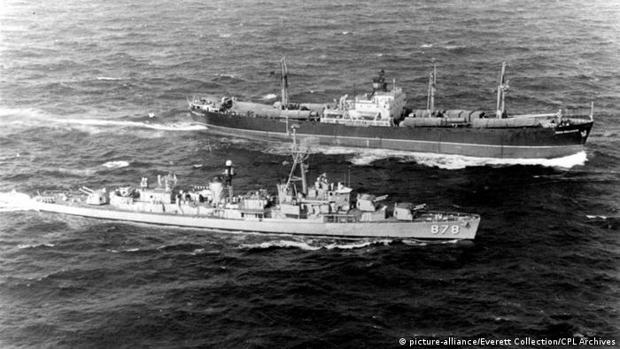 Kubakrise (1962) 11/10/62-Off coast of Cuba: The U.S.S. Vesole stears alongside the Soviet freighter Polznuov, for inspection of her cargo. On the deck are large ablong missile-like objects, two of which are partially uncovered.