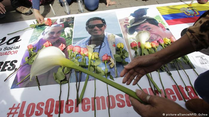 Women place flowers on pictures of three press workers after their deaths were confirmed.