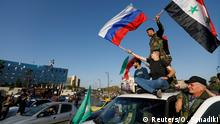 14.04.2018 Syrians wave Russian and Syrian flags during a protest against U.S.-led air strikes in Damascus,Syria April 14,2018.REUTERS/ Omar Sanadiki