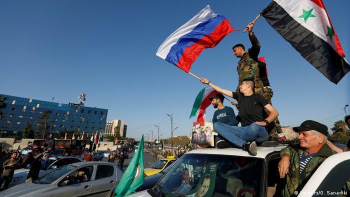 Başkent Şam'da Suriyeliler Rusya bayrakları ile operasyonu protesto etti