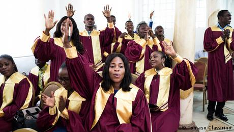 Young women and men in choir uniforms raise their hands in song (Tomaso Clavarino)